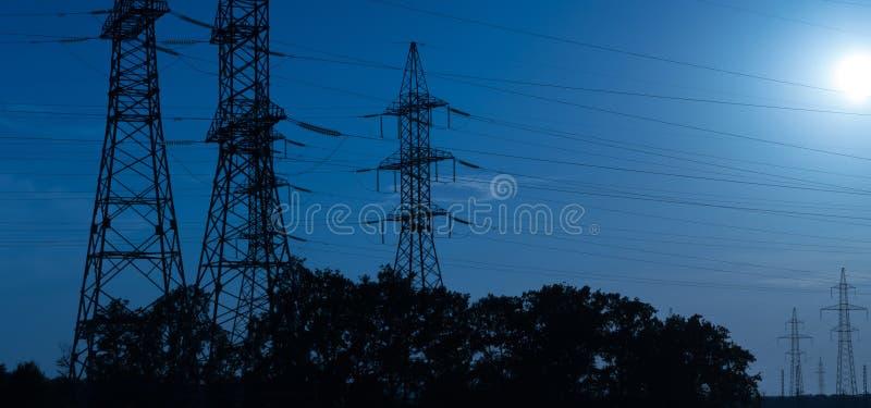 Wysokonapięciowe linie energetyczne w świetle promieni położenia słońce, odtransportowanie elektryczność nad długimi odległościam fotografia royalty free
