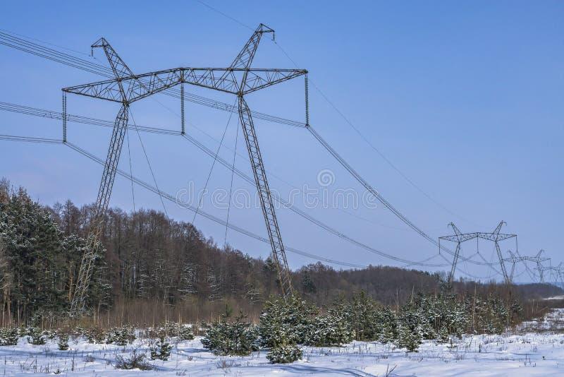 Wysokonapięciowe linie energetyczne w zima czasie Wysokiego woltażu przekazu wierza energii Elektryczny pilon obrazy royalty free