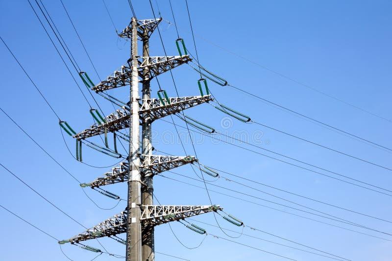Wysokonapięciowej linii energetycznej metalu popielaty wsparcie z dużo depeszuje pionowo widok nad jasnym bezchmurnym niebieskim  zdjęcia royalty free