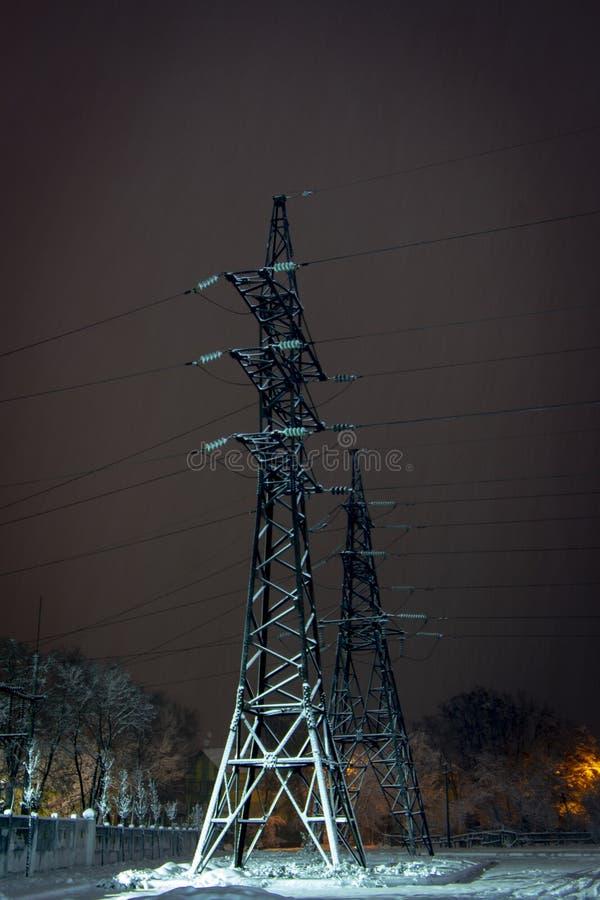 Wysokonapięciowi elektryczność pilony, linie energetyczne przy nocnym niebem i zdjęcie royalty free