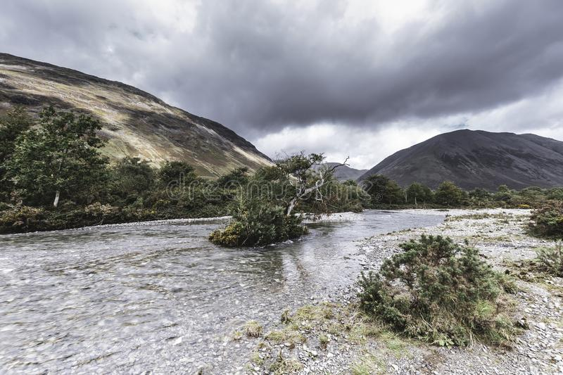 Wyspa z drzewem po środku spływanie strumienia Sceniczny krajobraz Jeziorny okręg, Cumbria, UK obrazy royalty free