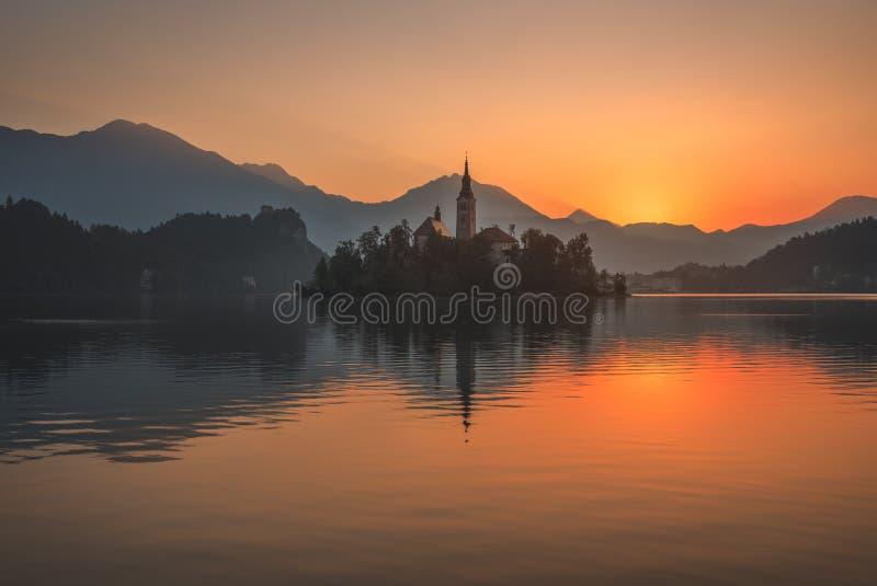 Wyspa z kościół w Krwawiącym jeziorze, Slovenia przy wschodem słońca obraz stock