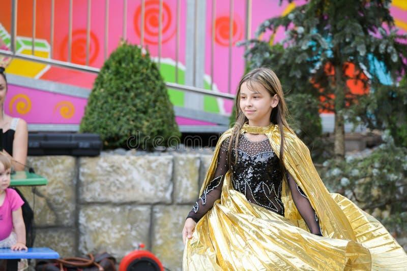 Występ młody tancerz Mała dziewczynka tana pozy Mowa młodą dziewczyną w czarnej sukni Huśtać się żółtego fan obrazy stock