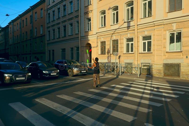 Występ uliczny juggler stoi przy rozdrożami przy zwyczajnym skrzyżowaniem przed samochodami obraz royalty free