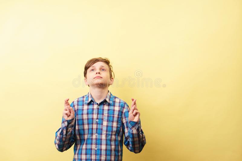 Występować z prośbą i nadzieja dla szczęścia chłopiec utrzymuje palce krzyżuje obrazy royalty free