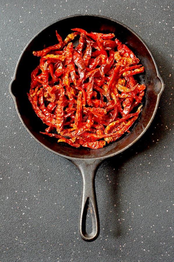 Wysuszeni czerwonego chili pieprze w ciskającej żelaznej smaży niecce, odgórny widok obraz stock