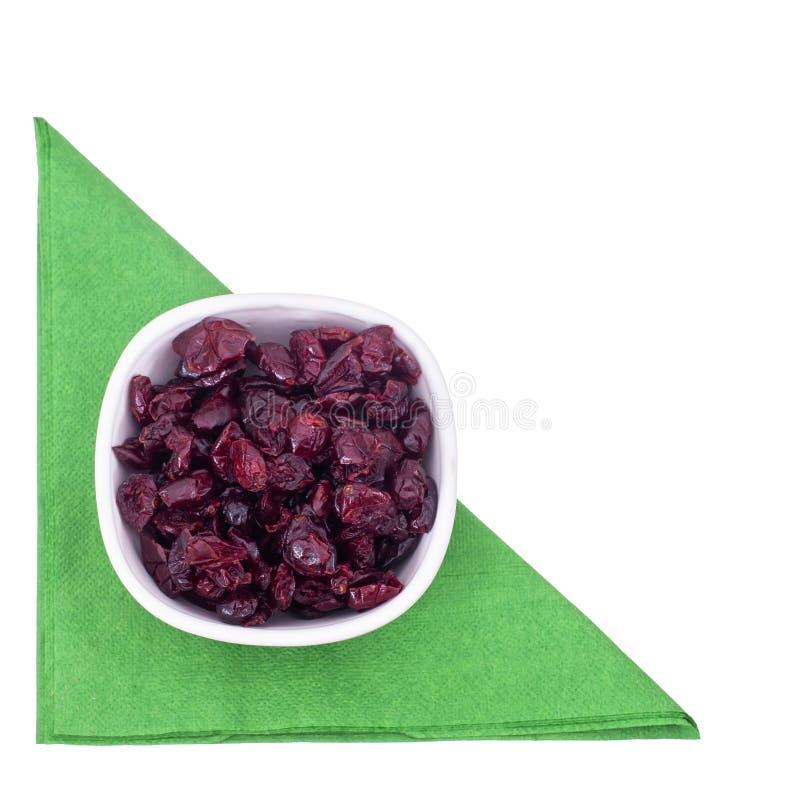 Wysuszeni czerwoni cranberries w pucharze na zielonym serviette, pielucha odizolowywająca na białym, odgórnym widoku, zdjęcie royalty free
