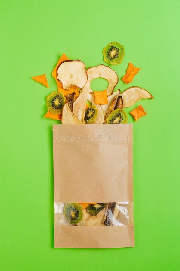 Wysuszeni owoc i warzywo plasterki w rzemiosło papierowej torbie na zielonym tle fotografia royalty free