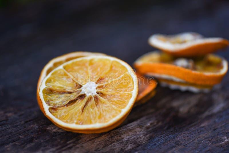 Wysuszeni pomarańcze plasterki na drewnianym zmroku zdjęcia royalty free