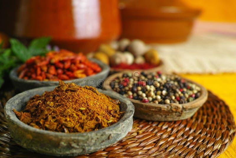 Wysuszona czerwień, gorący chili, czerń, biali pieprze w starych glinianych pucharach wewnątrz obraz royalty free