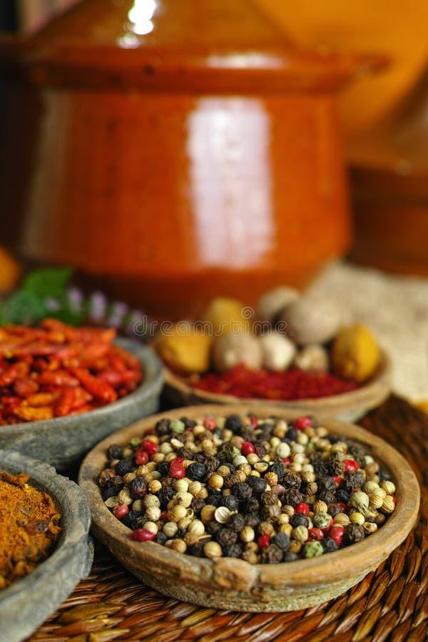Wysuszona czerwień, gorący chili, czerń, biali pieprze w starych glinianych pucharach wewnątrz obrazy stock