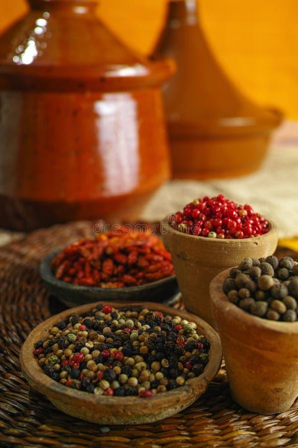 Wysuszona czerwień, gorący chili, czerń, biali pieprze w starych glinianych pucharach wewnątrz obraz stock