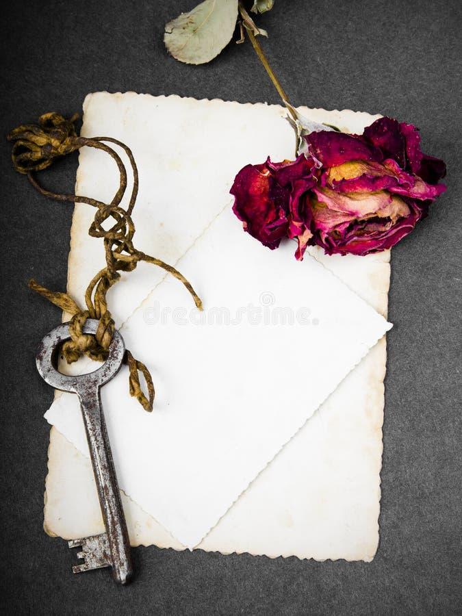 Wysuszona czerwieni róża, ośniedziały klucz i pusta fotografia, fotografia stock