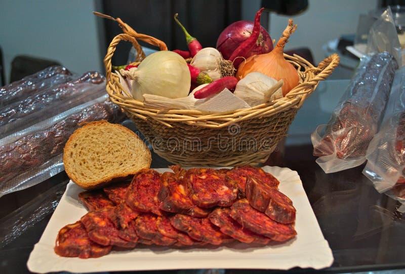Wysuszona pokrojona kiełbasa, chleb i kosz zdjęcie royalty free