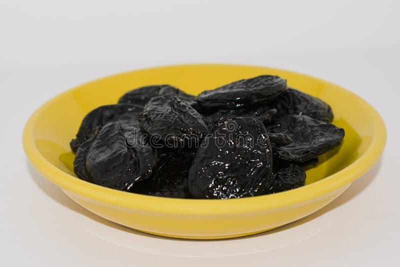 Wysuszone czarne śliwki na żółtym ceramicznym talerzu obrazy stock