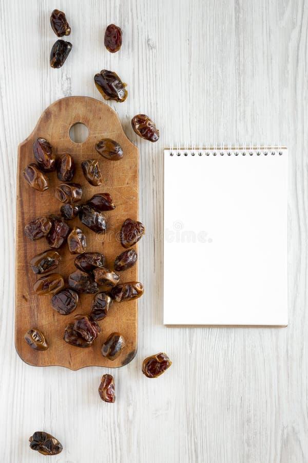 Wysuszone daty na nieociosanej drewnianej desce, pusty notepad nad białą drewnianą powierzchnią, odgórny widok Od above, koszt st zdjęcie stock