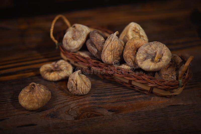 Wysuszone figi w małym koszu na drewnianym tle fotografia royalty free