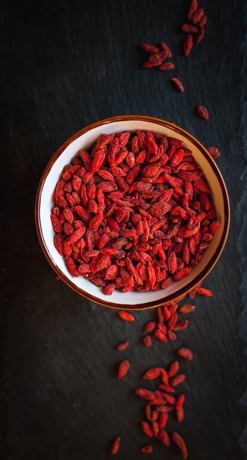 Wysuszone goji jagody w pucharze na ciemnym tle, odgórny widok zdjęcie stock