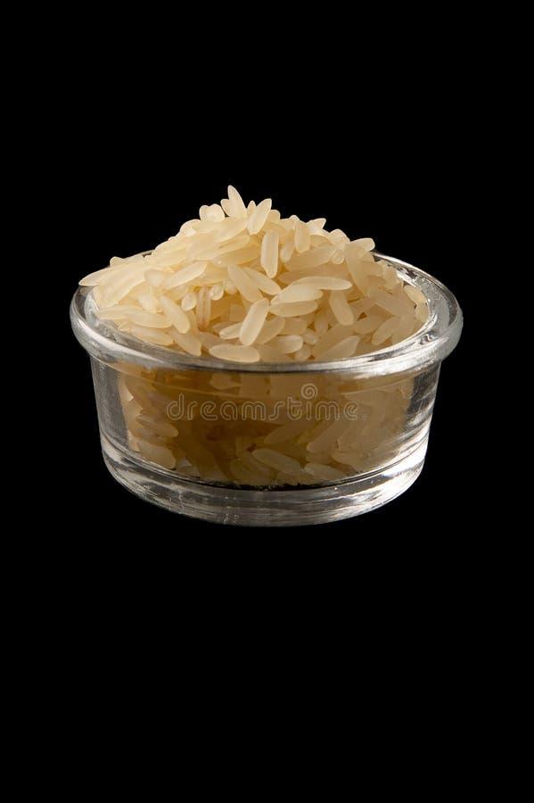 Wysuszony świeży ryż groszkuje na cristal pucharze nad czarnym tłem obraz stock