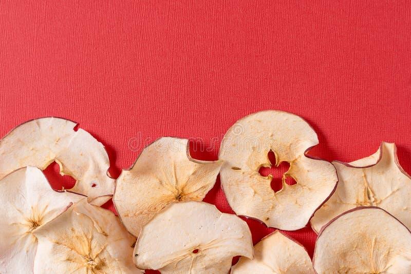 Wysuszony jabłko szczerbi się nad czerwonym tłem z kopii przestrzenią zdjęcie royalty free
