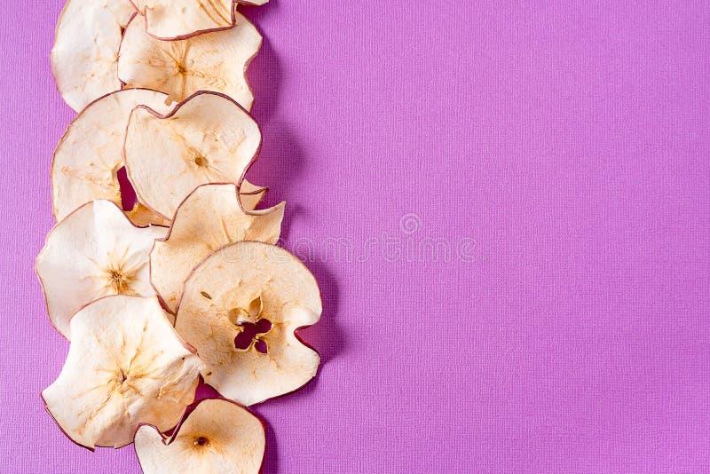 Wysuszony jabłko szczerbi się nad purpurowym tłem z kopii przestrzenią fotografia royalty free