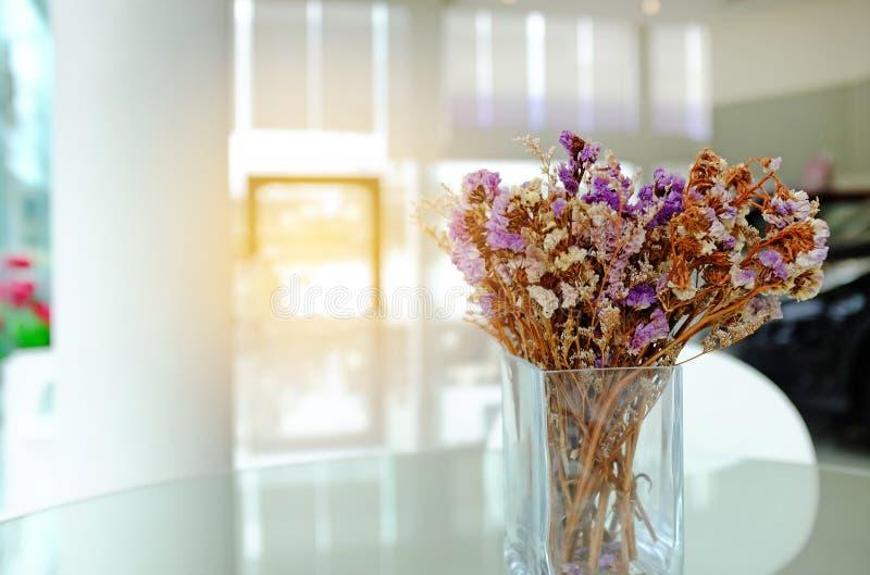 Wysuszony purpura kwiat w szklanym garnku dla biurowej dekoracji na stole z kopii przestrzenią światłem słonecznym i obraz royalty free