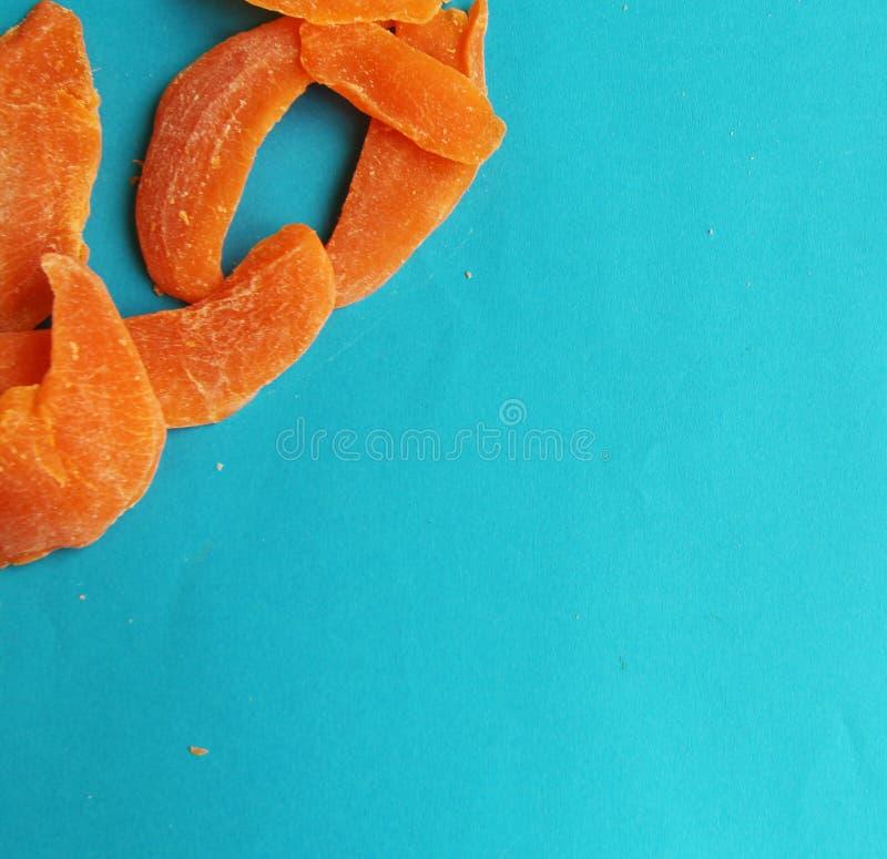 Wysuszonych owoc mangowy pomarańczowy plasterek na błękitnym jaskrawym tle Smakowity yummy dieting obraz royalty free