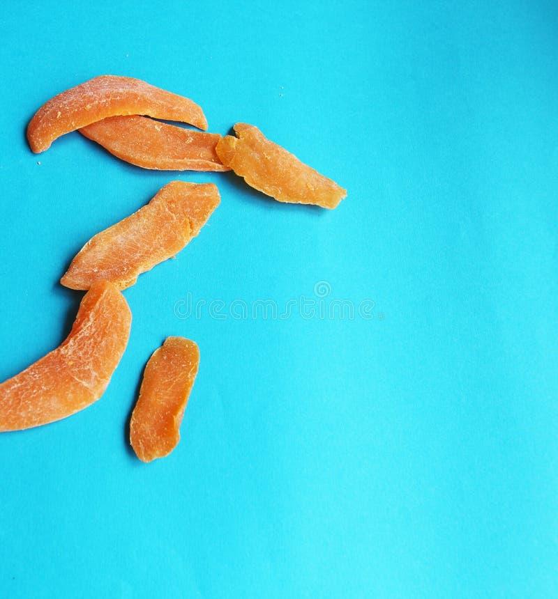 Wysuszonych owoc mangowy pomarańczowy plasterek na błękitnym jaskrawym tle Smakowity yummy dieting zdjęcie stock