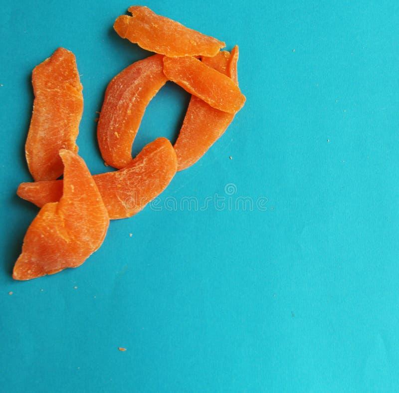 Wysuszonych owoc mangowy pomarańczowy plasterek na błękitnym jaskrawym tle Smakowity yummy dieting obrazy stock