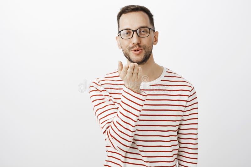 Wysyłać buziaki ty Portret śliczny atrakcyjny homoseksualista w szkłach, trzymający palmowego pobliskiego usta i podmuchowego mwa obraz royalty free