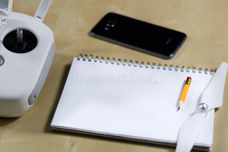 Wysyła latanie i akcesoria na drewnianym stole Trutnia notatnik zdjęcie royalty free