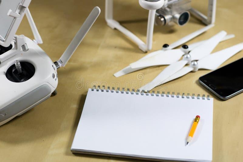 Wysyła latanie i akcesoria na drewnianym stole Trutnia notatnik obraz stock