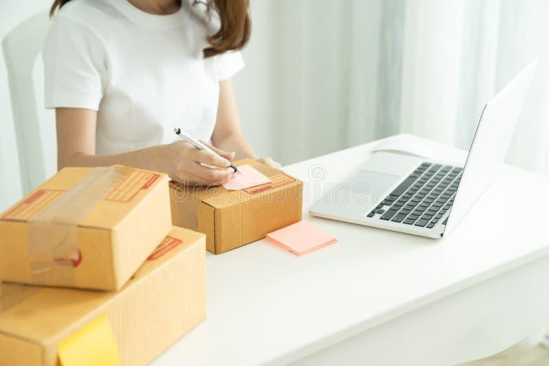 Wysyłki robić zakupy online, potomstwa zaczyna up małego biznesu właściciela writing adres na kartonie przy miejscem pracy fotografia royalty free