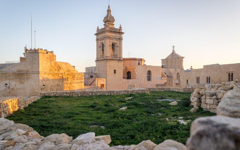 Wyszczególnia widok na starej, dziejowej St Joseph kaplicie wśrodku cytadeli Wiktoria wśrodku antyk ruin ścian z trawy polem, obraz royalty free