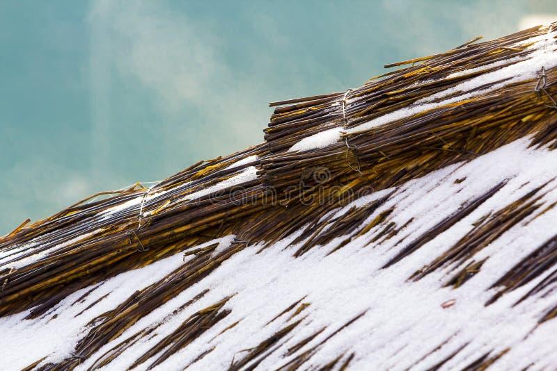 Wyszczególnia obrazek robić od słomy z śniegiem na nim dach obraz stock