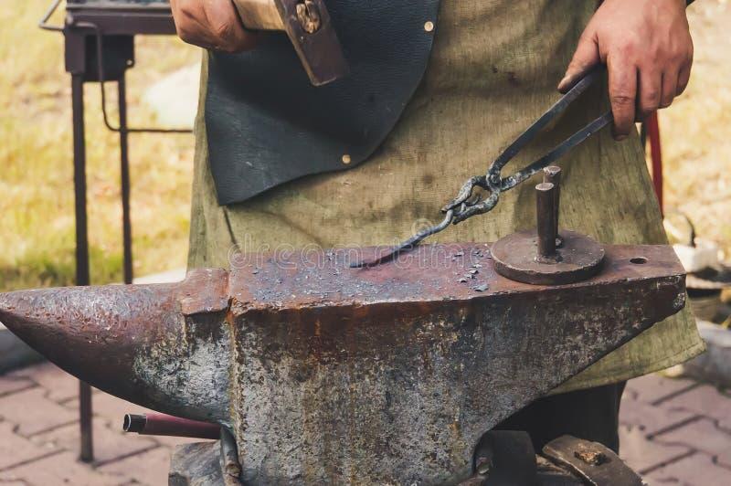 Wyszczególnia strzał młoteczkowego skucia gorący żelazo przy kowadłem zdjęcie stock