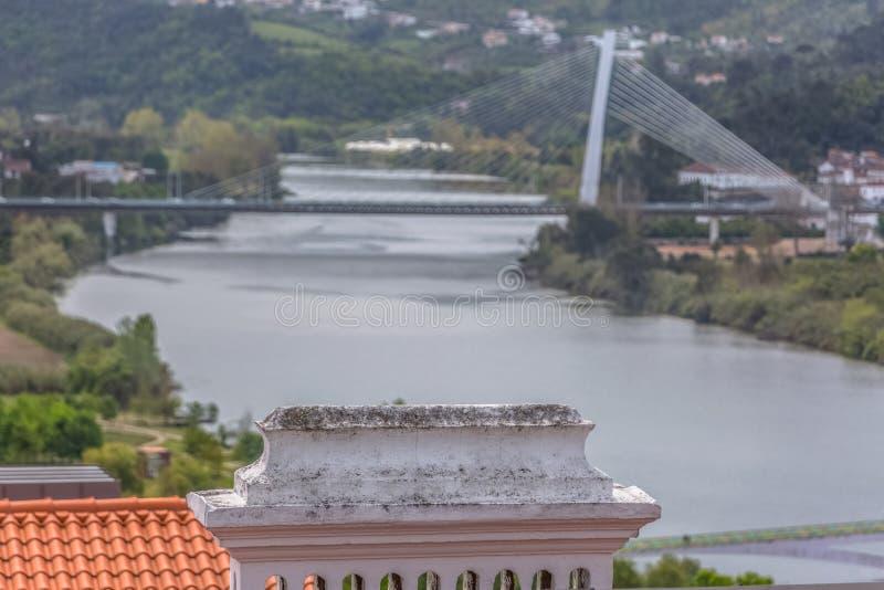 Wyszczególnia widok tradycyjny komin z zamazaną Mondego rzeką i Rainha Santa Isabel mostem, jako tło w Coimbra, Portugalia obraz stock
