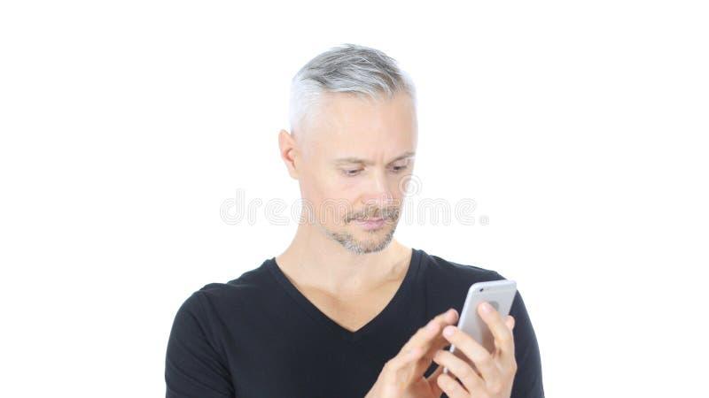 Wyszukujący Online na telefonie, W Średnim Wieku mężczyzna, Biały tło obrazy royalty free