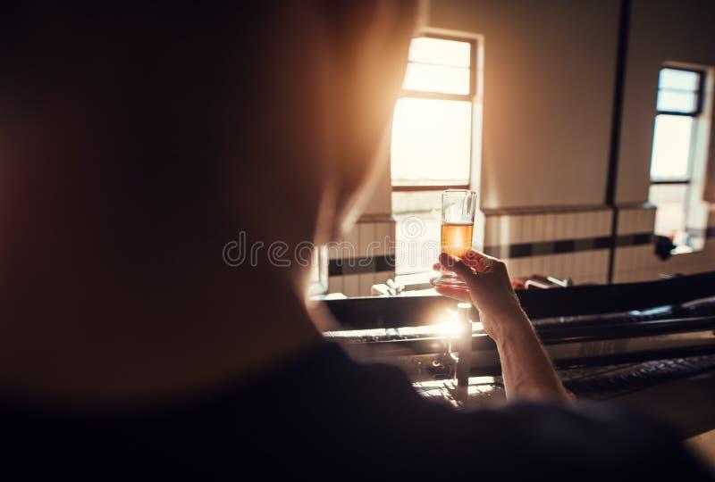 Wytwórca egzamininuje piwo w szkle przy browarem zdjęcia royalty free