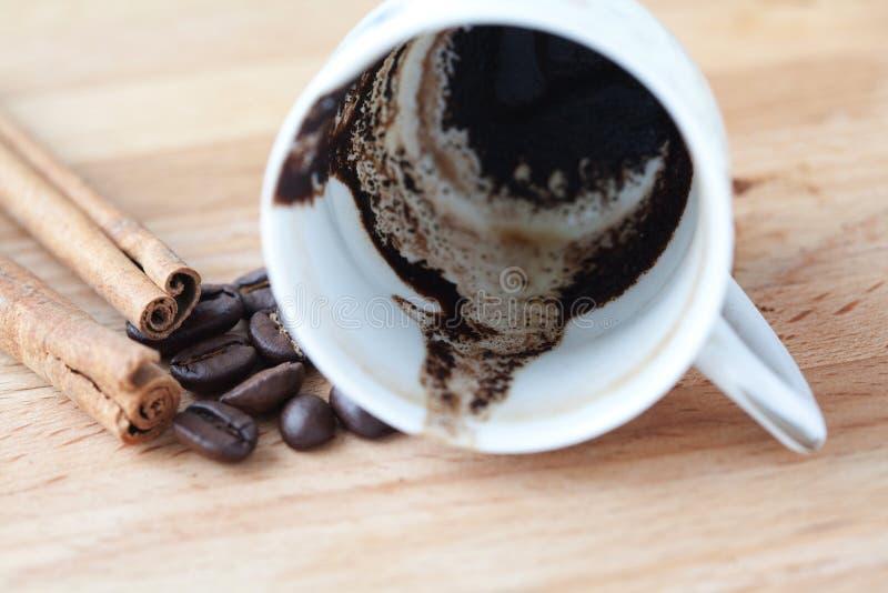 Wywrócona filiżanka kawy Kawowe ziemie i fasole miękka ostrość, drewniany tło zdjęcia royalty free