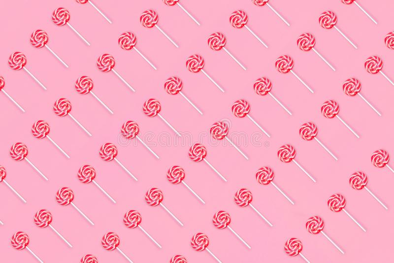 Wzór kolorowy lizaka cukierek z kijem na miękkich części menchii tle Mieszkanie nieatutowy zdjęcia stock