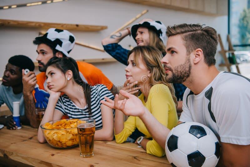 wzburzeni młodzi wielokulturowi przyjaciele w piłki nożnej piłki kapeluszach z ręki fan i clappers uzbrajać w rogi oglądający fut zdjęcia stock