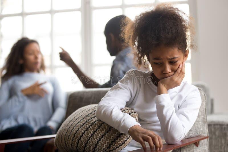 Wzburzona amerykanin afrykańskiego pochodzenia dziewczyna siedzi samotnie, rodziców kłócić się zdjęcie royalty free