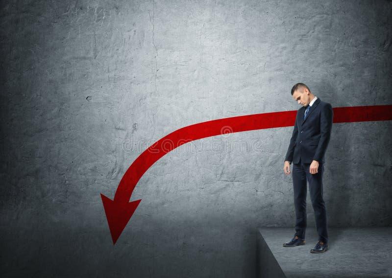 Wzburzona biznesmen pozycja na krawędzi bezdenności z czerwony strzałkowaty iść w dół obraz stock