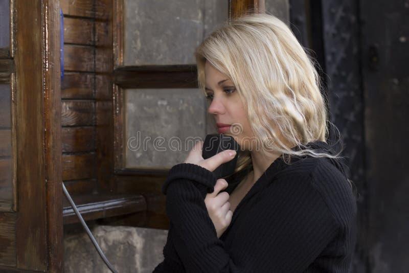 Wzburzona blondynki kobieta blisko wynagrodzenie telefonu zdjęcia stock