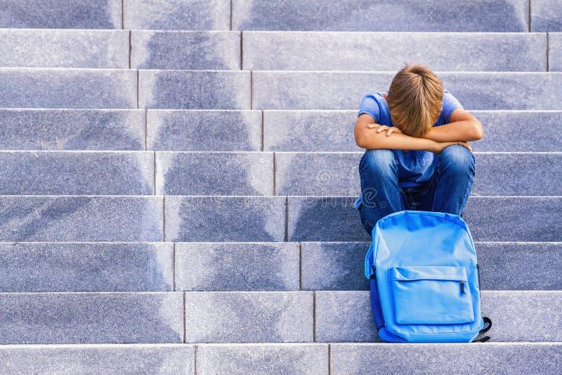 Wzburzona chłopiec siedzi na schodkach outdoors zakrywał jego twarz z rękami zdjęcie stock