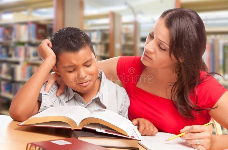 Wzburzona Latynoska Młoda chłopiec i Famle Dorosły studiowanie Przy biblioteką zdjęcie royalty free