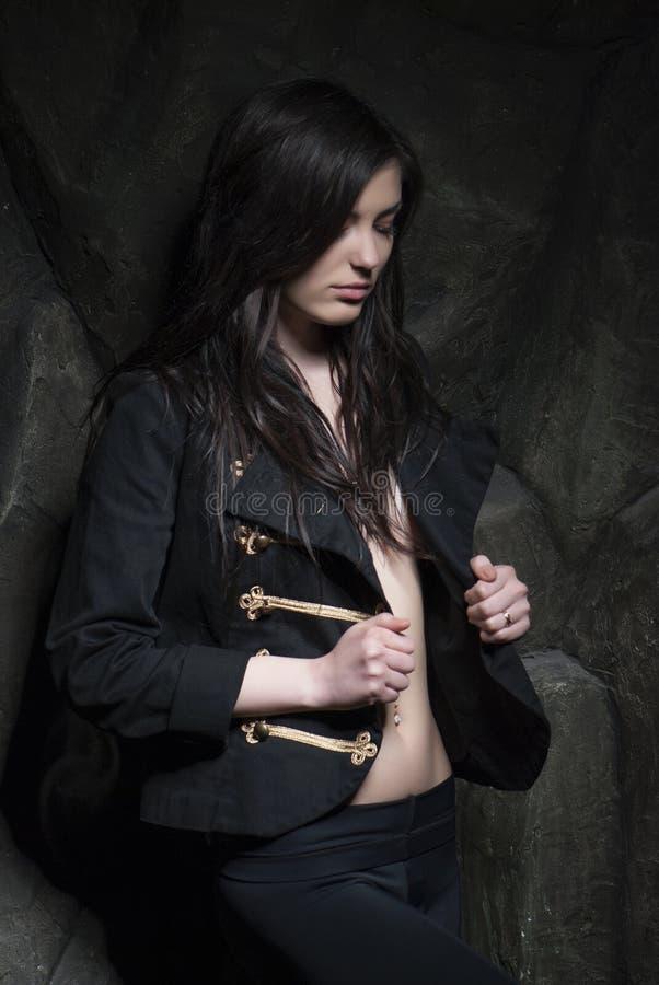 Wzburzona młoda dziewczyna pozuje w militarnej kurtce nad rockowym tłem obraz stock