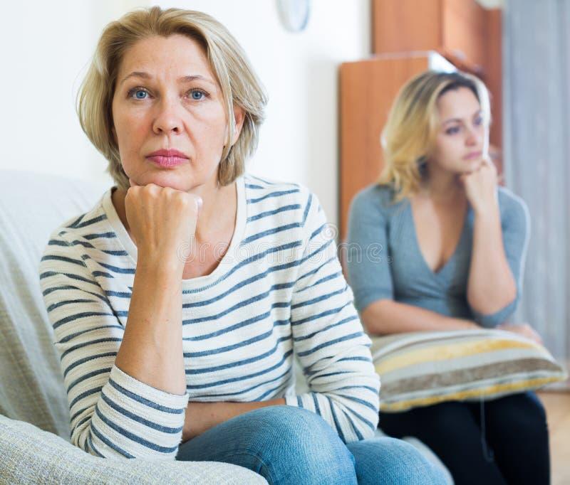 Wzburzona młoda kobieta i senior matkujemy mieć bad dyskutujemy salowego fotografia royalty free