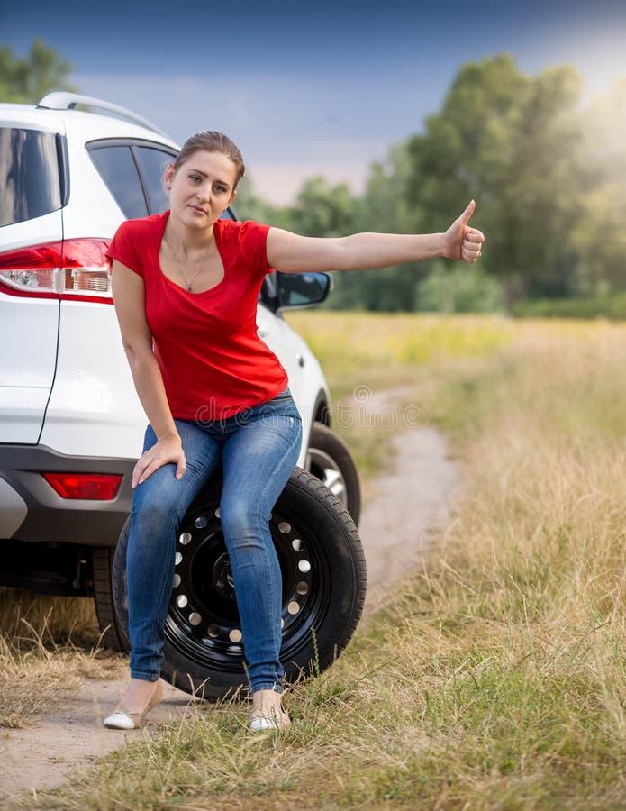 Wzburzona młoda kobieta z łamanym samochodowym mienie kciukiem up i autostopem obrazy stock